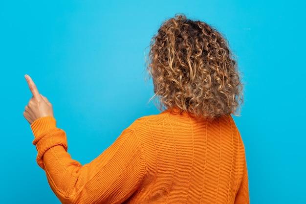 Vrouw van middelbare leeftijd staande en wijst naar bezwaar op kopie ruimte, achteraanzicht