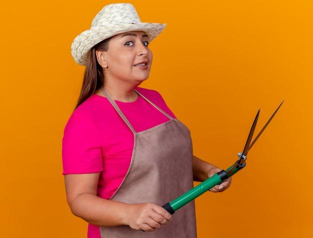 Vrouw van middelbare leeftijd tuinman in schort en hoed met heggenschaar kijken camera lachend met blij gezicht staande over oranje achtergrond