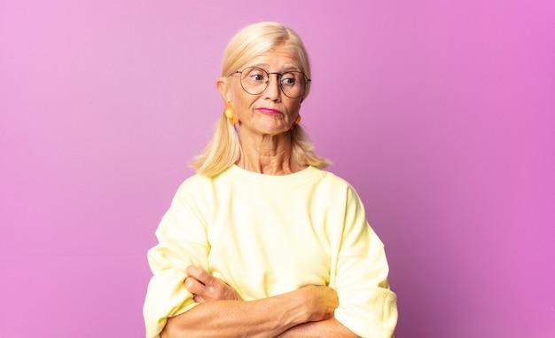 Vrouw van middelbare leeftijd twijfelt of denkt, bijt op lip en voelt zich onzeker en nerveus, op zoek naar ruimte aan de zijkant