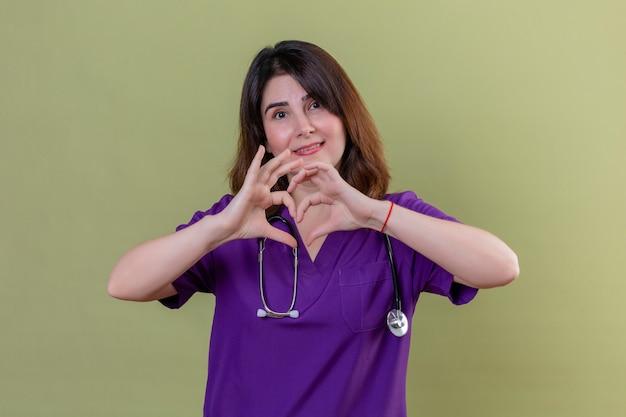 Vrouw van middelbare leeftijd verpleegster uniform dragen en met een stethoscoop romantisch hart gebaar maken over de borst, met een glimlach op het gezicht over geïsoleerde groene muur