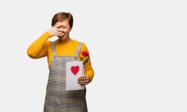 Vrouw van middelbare leeftijd vieren valentijnsdag pijnlijk en lachen op hetzelfde moment