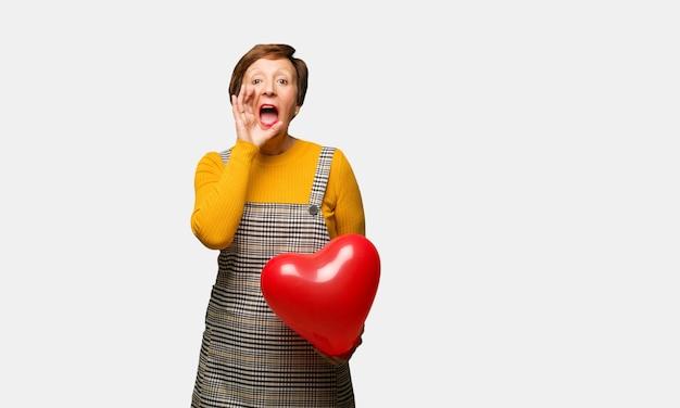 Vrouw van middelbare leeftijd vieren valentijnsdag schreeuwen iets blij naar de voorkant