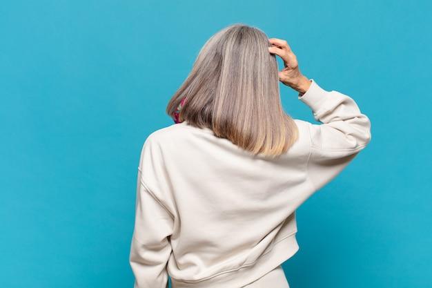 Vrouw van middelbare leeftijd voelt zich geen idee en verward, denkt een oplossing, met de hand op de heup en de andere op het hoofd, zicht naar achteren