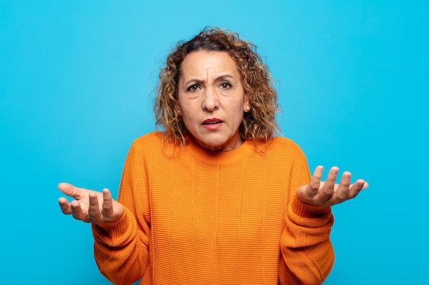 Vrouw van middelbare leeftijd voelt zich geen idee en verward, niet zeker welke keuze of optie ze moet kiezen, zich afvragend