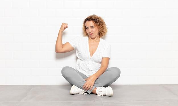 Vrouw van middelbare leeftijd voelt zich gelukkig, tevreden en krachtig, buigt fit en gespierde biceps, ziet er sterk uit na de sportschool