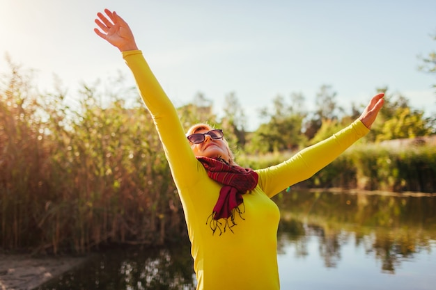 Vrouw van middelbare leeftijd voelt zich vrij en gelukkig op de oever van de rivier op herfstdag. hogere dame die handen opheft. harmonie en balans met de natuur