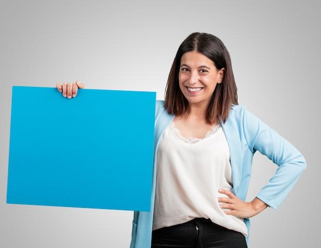 Vrouw van middelbare leeftijd, vrolijk en gemotiveerd, toont een lege poster waar je een bericht kunt laten zien, communicatieconcept