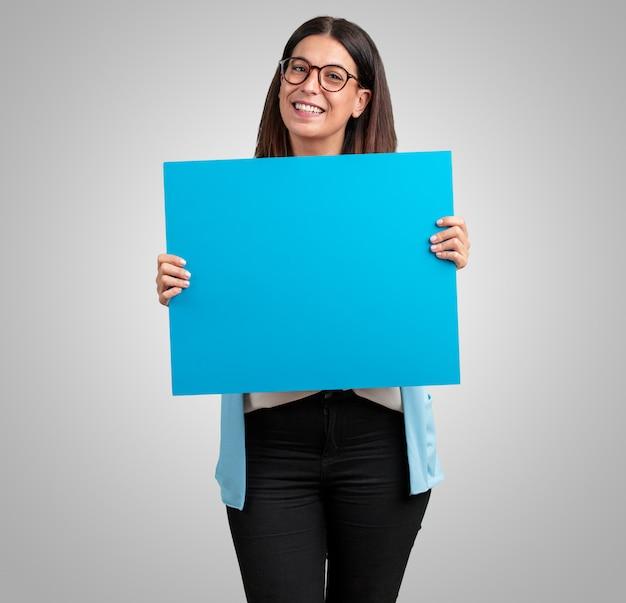 Vrouw van middelbare leeftijd, vrolijk en gemotiveerd, toont een lege poster waar je een mes kunt laten zien