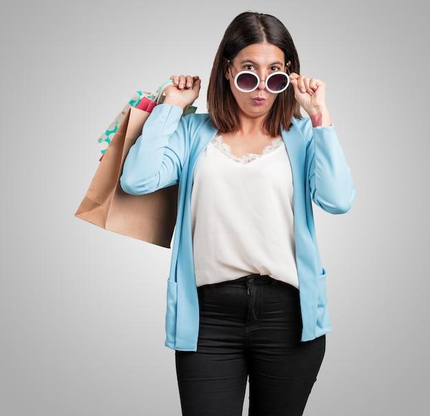 Vrouw van middelbare leeftijd, vrolijk en lachend, erg opgewonden met een boodschappentas