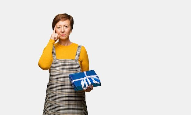 Vrouw van middelbare leeftijd vrouw vieren valentijnsdag een concentratie gebaar doen