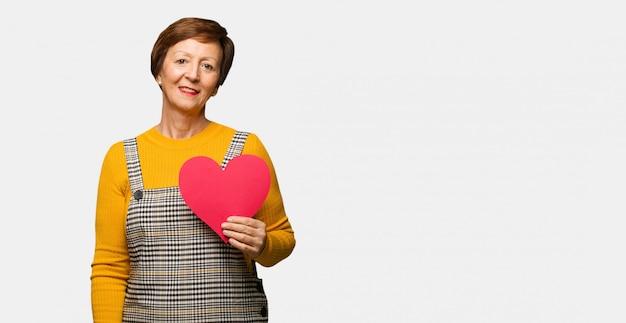 Vrouw van middelbare leeftijd vrouw vieren valentijnsdag vrolijk met een grote glimlach