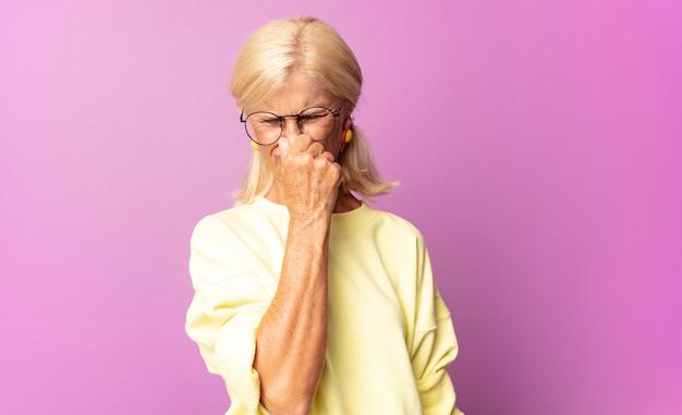 Vrouw van middelbare leeftijd walgt en houdt neus vast om te voorkomen dat ze een vieze en onaangename stank ruikt