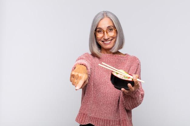 Vrouw van middelbare leeftijd wijzend op de camera met een tevreden, zelfverzekerde, vriendelijke glimlach, die je aziatisch voedselconcept kiest