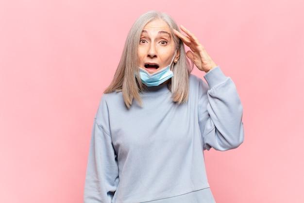 Vrouw van middelbare leeftijd ziet er blij, verbaasd en verrast uit, lacht en realiseert zich geweldig en ongelooflijk goed nieuws