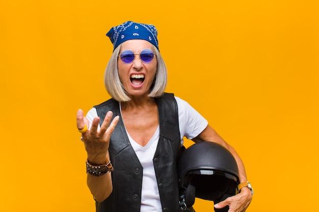 Vrouw van middelbare leeftijd ziet er boos, geïrriteerd en gefrustreerd uit en schreeuwt wtf of wat is er mis met je