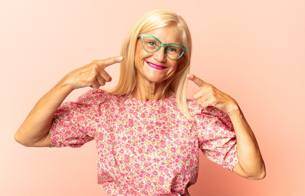 Vrouw van middelbare leeftijd ziet er boos, gestrest en geïrriteerd uit en bedekt beide oren met een oorverdovend geluid, geluid of luide muziek