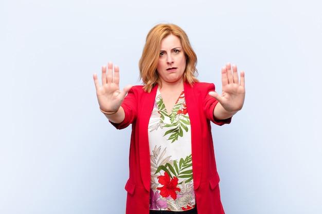 Vrouw van middelbare leeftijd ziet er ernstig, ongelukkig, boos en ontevreden uit en verbiedt de toegang of zegt stop met beide open handpalmen