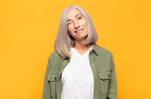 Vrouw van middelbare leeftijd ziet er gelukkig en vriendelijk uit, lacht en knipoogt naar je met een positieve instelling
