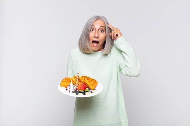 Vrouw van middelbare leeftijd ziet er gelukkig, verbaasd en verrast uit, lacht en realiseert zich geweldig en ongelooflijk goed nieuws. ontbijt concept