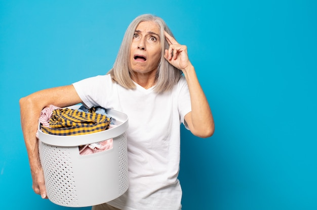 Vrouw van middelbare leeftijd ziet er gelukkig, verbaasd en verrast uit, lacht en realiseert zich geweldig en ongelooflijk goed nieuws
