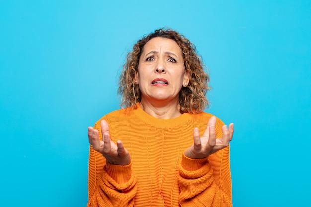 Vrouw van middelbare leeftijd ziet er wanhopig en gefrustreerd uit, gestrest, ongelukkig en geïrriteerd, schreeuwend en schreeuwend