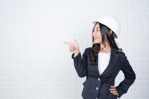 Vrouw van techniek die een hoed houdt, scheid de witte bakstenen muur gemaakte gebaren met gebarentaal.