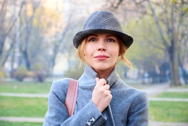 Vrouw van veertig jaar met jas en hoed in het voorjaar