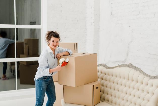 Vrouw vastmakende kleverige band aan doos