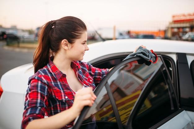 Vrouw veegt auto af na het wassen op self-carwash. dame schoonmaak voertuig
