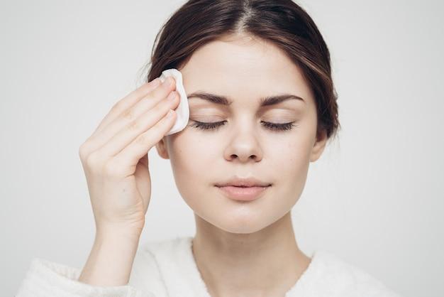 Vrouw veegt haar gezicht af met een wit, zacht sponsmodel voor schoonheidsverzorging
