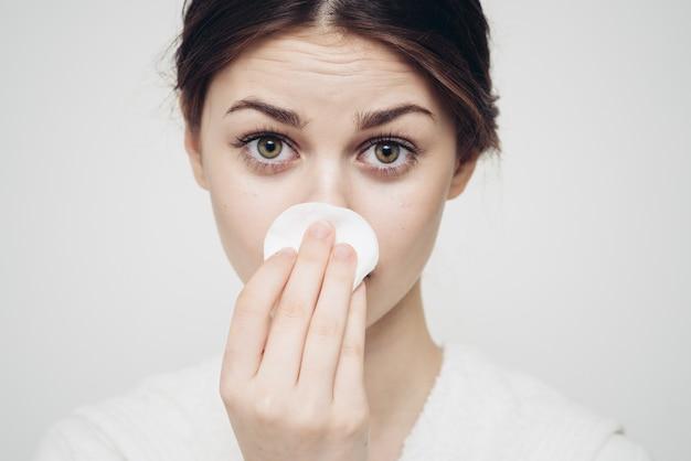 Vrouw veegt haar gezicht af met een witte zachte spons