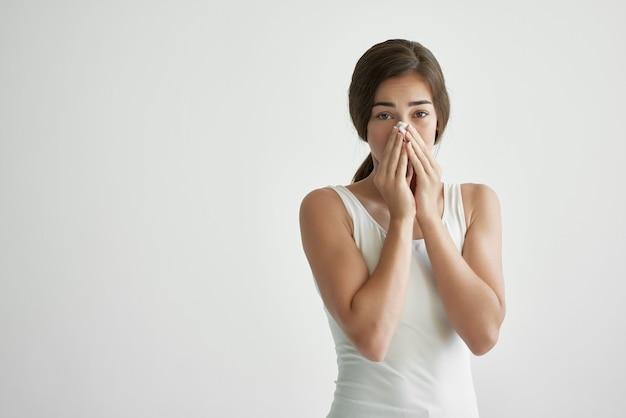 Vrouw veegt haar neus af met een zakdoek allergie loopneus gezondheidsproblemen