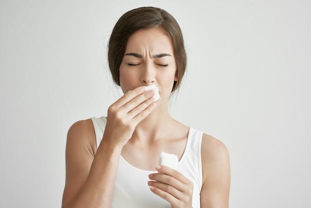 Vrouw veegt haar neus af met een zakdoek loopneus gezondheidsproblemen gezondheid verkoudheid