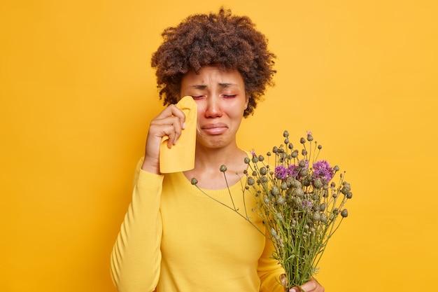 Vrouw veegt tranen af heeft rode opzwellende ogen allergisch voor pollen lijdt aan seizoensgebonden allergie houdt wilde bloemen geïsoleerd op geel