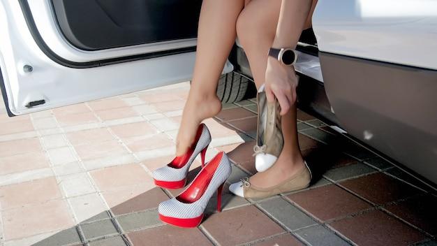 Vrouw veranderende schoenen na het besturen van een auto.