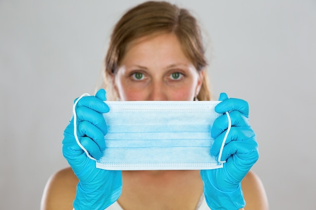 Vrouw verbergt haar gezicht achter chirurgisch masker voor haar