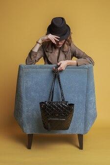 Vrouw verbergt haar gezicht onder de hoed en zit op een blauwe stoel met een zwarte plunjezak in haar armen.