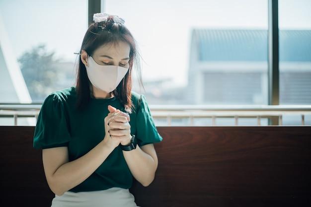 Vrouw verblijf in de kerk met gezichtsmasker om te beschermen