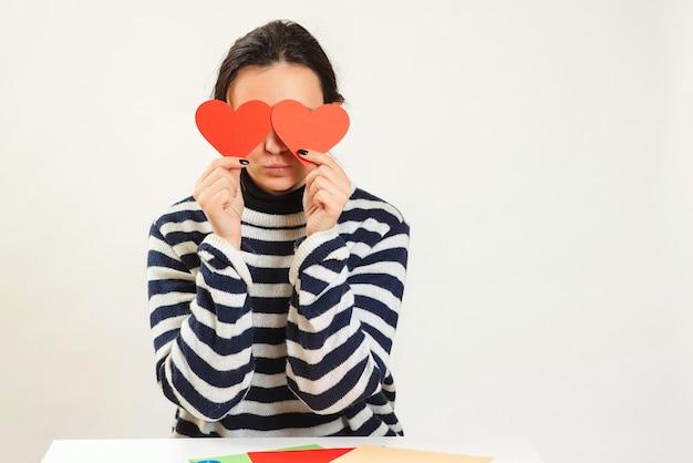 Vrouw verblind door grote liefde. jong wijfje dat rode harten over ogen houdt en glimlacht.
