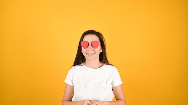 Vrouw verblind door liefde, op een gele achtergrond.