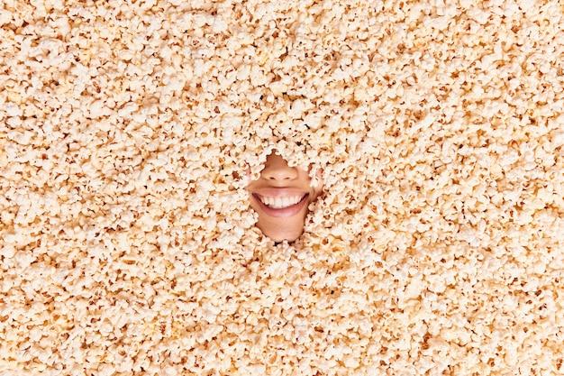Vrouw verborgen in popcorn glimlacht breed toont witte tanden die film gaan kijken in de bioscoop heeft een vrolijke bui. onherkenbaar vrouwtje kegel met heerlijke snack. uitzicht van boven