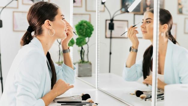 Vrouw verft haar wenkbrauwen terwijl ze in een spiegel in een schoonheidssalon kijkt