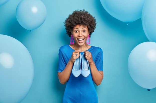 Vrouw verkleedt zich voor speciale gelegenheid kiest schoenen met hoge hakken om te dragen bereidt zich voor op feest geïsoleerd op blauw Gratis Foto