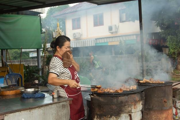 Vrouw verkoopt gegrild varkensvlees op het fornuis.