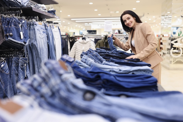 Vrouw verkoper legt jeans in etalage