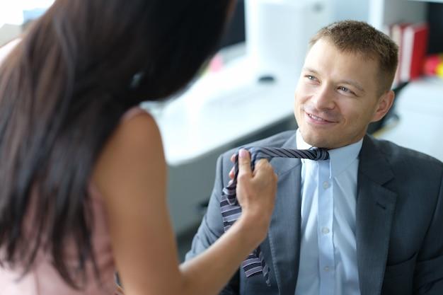 Vrouw verleidt en trekt stropdas van jonge lachende baas
