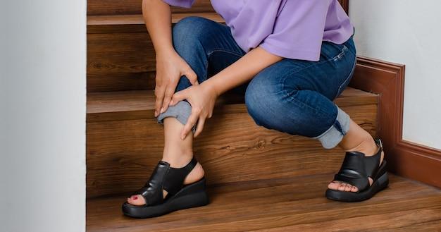 Vrouw verliest de controle en kan niet op trappen lopen, ze stopt en houdt haar benen vast voor steun en rust met een tintelend gevoel. concept van guillain-barre-syndroom en gevoelloze benenziekte of vaccin-bijwerking.