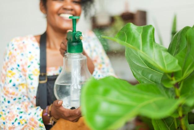 Vrouw vernevelt planten met een waterstraal in een plantenwinkel