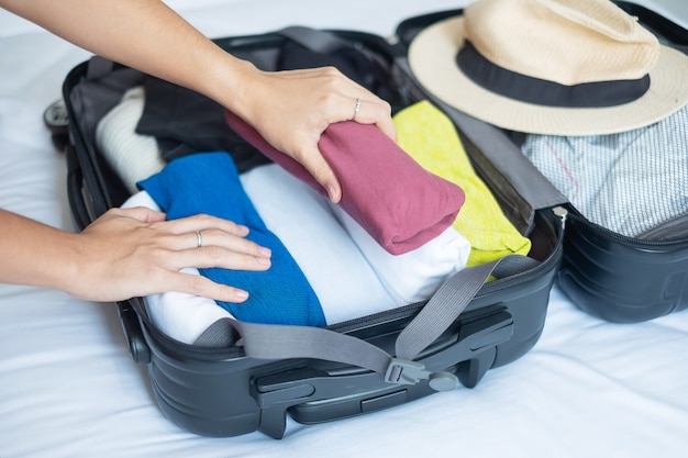 Vrouw verpakking bagage op het bed