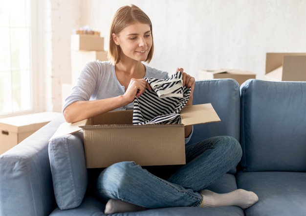 Vrouw verpakking doos met kleren om te verhuizen